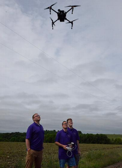 Nick Davis pilots a drone at an Andover farm; students Tim Mahany (left) and Justin Smith look on.
