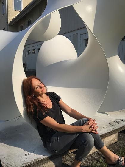 Eva Hild, with her sculpture, Wave, which is being installed outside the Alfred Ceramic Art Museum