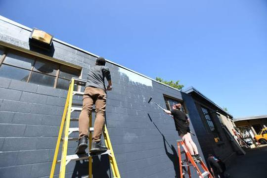 Workers paint the exterior of the new, temporary home of the National Casting Center Foundry.