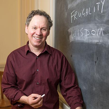 Professor Westacott standing next to a chalked up blackboard.