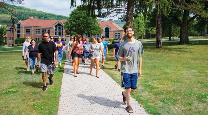 student leading a tour group through campus