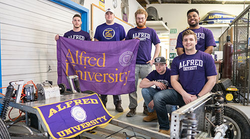 Students in Alfred Gear with an AlfredU flag