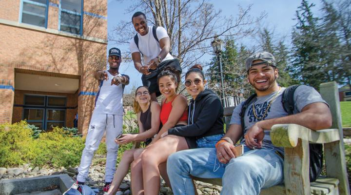 students smiling and posing for a photo together on a bench